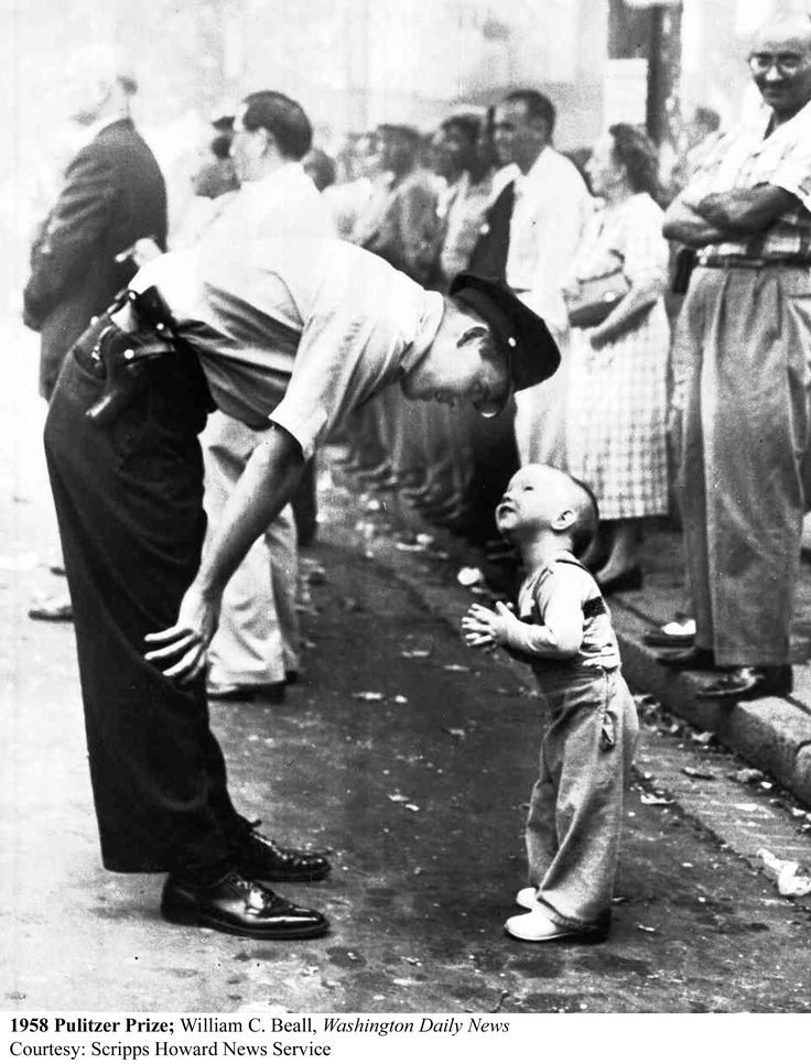 pulitzer prize photo 1958 (Police man talking to a young boy at a parade)- I just love this. Especially the man smiling in the background.