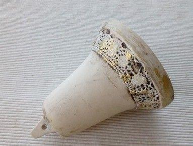 Odlívaný zvonek, zdobený krajkou a zlatou patinou. Skvěle pasuje do