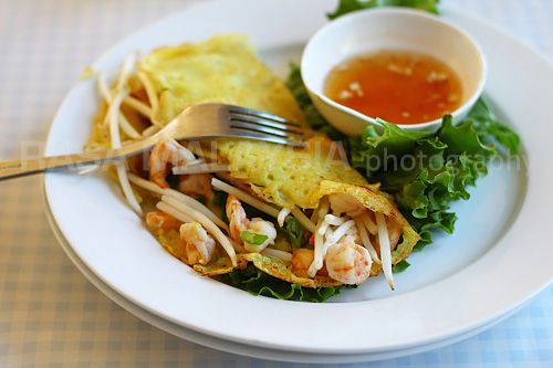 """Banh xeo is a southern Vietnam recipe. Xeo means """"sizzling"""" so it's also known as sizzling Saigon crepes.  To eat, just wrap it with a lettuce leaf and herbs (Thai basil, Perilla herb, mint leaves) and then dip in nuoc cham, the ubiquitous Vietnamese dipping sauce made of fish sauce, lime juice, and sugar."""