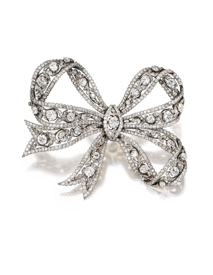 PLATINUM, GOLD AND DIAMOND BOW BROOCH, CIRCA 1910. The delicate three-loop bow of openwork design set with 34 old European-cut diamonds weighing approximately 9.50 carats, accented by numerous smaller old European-cut diamonds weighing approximately 21.25 carats.