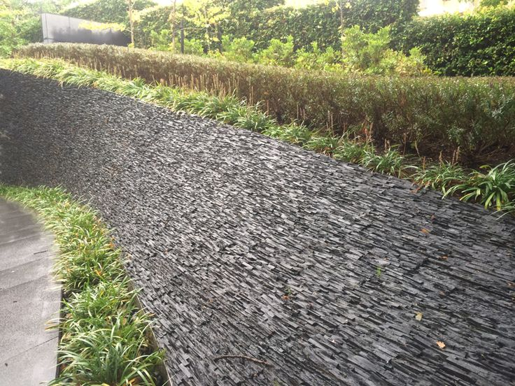 The dramatic effect has been created using for #stackedstone on this sloping retaining wall next to the driveway entrance.