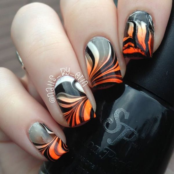 Fiery and a sure stand out, this water marble nail art design plays around with the orange, white and black color combination.