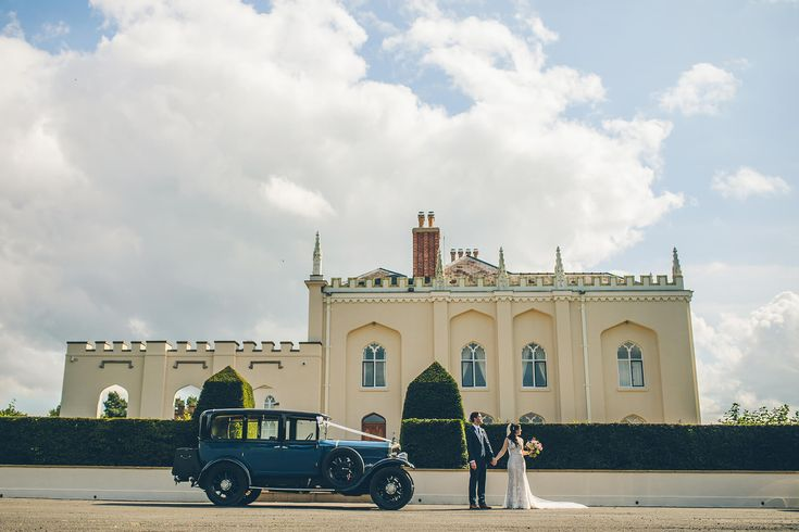 A bride and groom stand next to a vintage wedding car in front of the North Wing