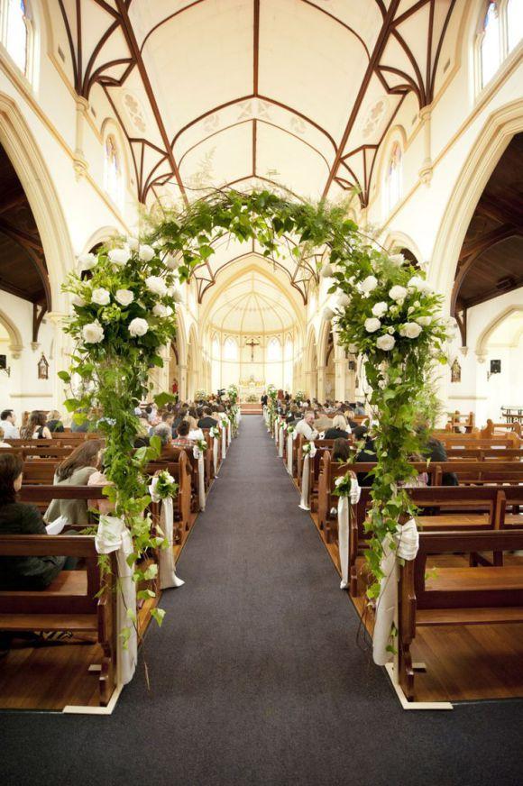 Arco no corredor da igreja decorado com folhas e flores