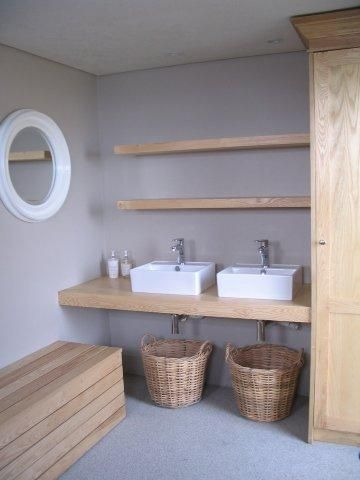 Creative storage solutions in contemporary, earthy bathroom.  Seaside holiday home.