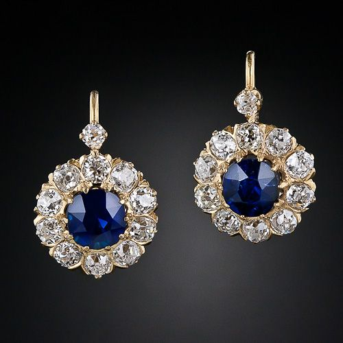 pair of true electric blue sapphires, together weighing 2.35 carats, radiate from within sparkling diamond halos and are surmounted by a single glistening diamond, in these original 18 karat yellow gold, classic Victorian earrings, circa 1885.