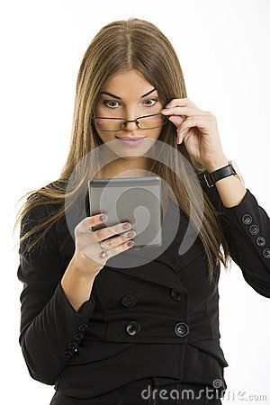 Beautiful surprised long-haired young woman looking over her eyeglasses at her e-book reader display over white background.