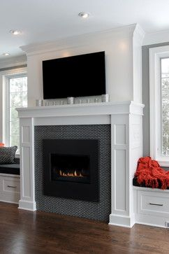 Fireplace with full wood surround and mantel between two windows and window seats