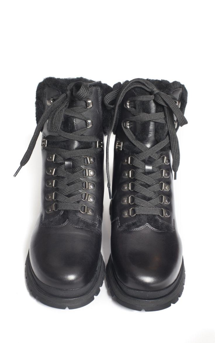 """Boots style """"Montagne"""" Prada Ces grosse boots style montage sont signées Prada pour l'automne-hiver 2017-2018. Ces boots sont typiques avec leurs grosses semelles de 3 cm en caoutchouc noir crantées et leur cuir épais avec des crochets pour lacer les lacets. Elles présentent aussi de la fourrure afin de garder vos petits pieds bien au chaud tout l'hiver. Cuir + fourrure"""