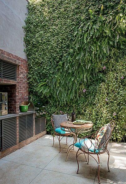 """No espaço gourmet, os moradores fazem pizza e churrasco. Faltava um jardim. A paisagista Bia Breu revestiu as paredes com plantas, que o casal avista da cama, no andar de cima. """"Queria a sensação de não estar na cidade"""", diz Fabiano Rodrigues Ribeiro"""