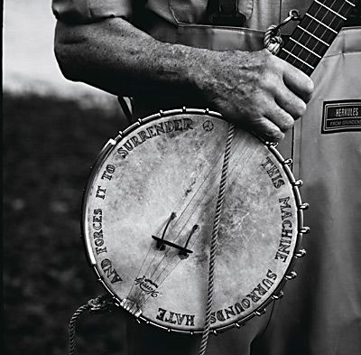 "Pete Seeger's banjo. It says: ""This machine surrounds hate and forces it to surrender."""
