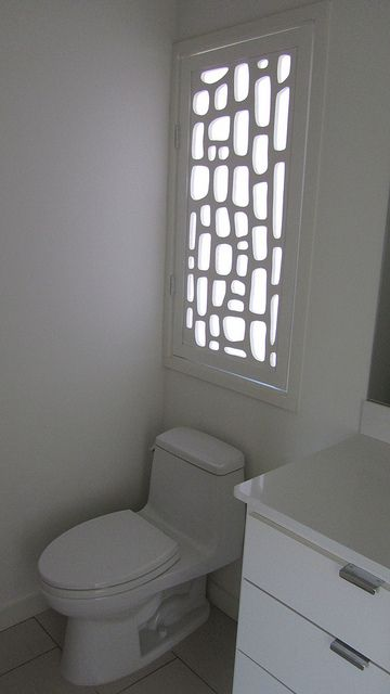 Bathroom window cover opens like a cabinet.  This is a great idea for the master bathroom.