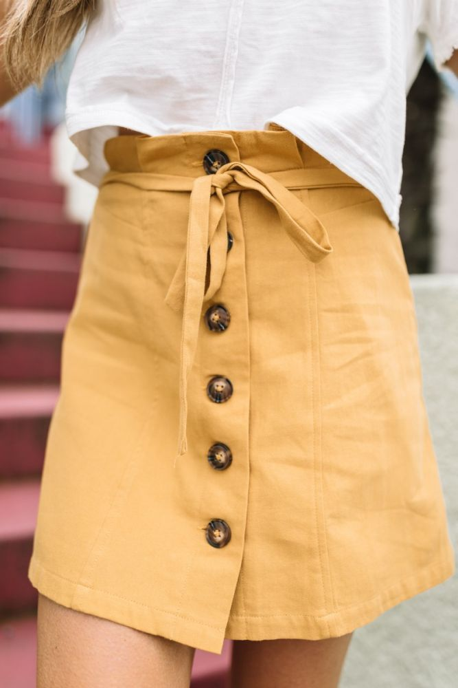 close-up view. mustard mini skirt with tie belt and buttons down the front. – • N E W • A R R I V A L S •