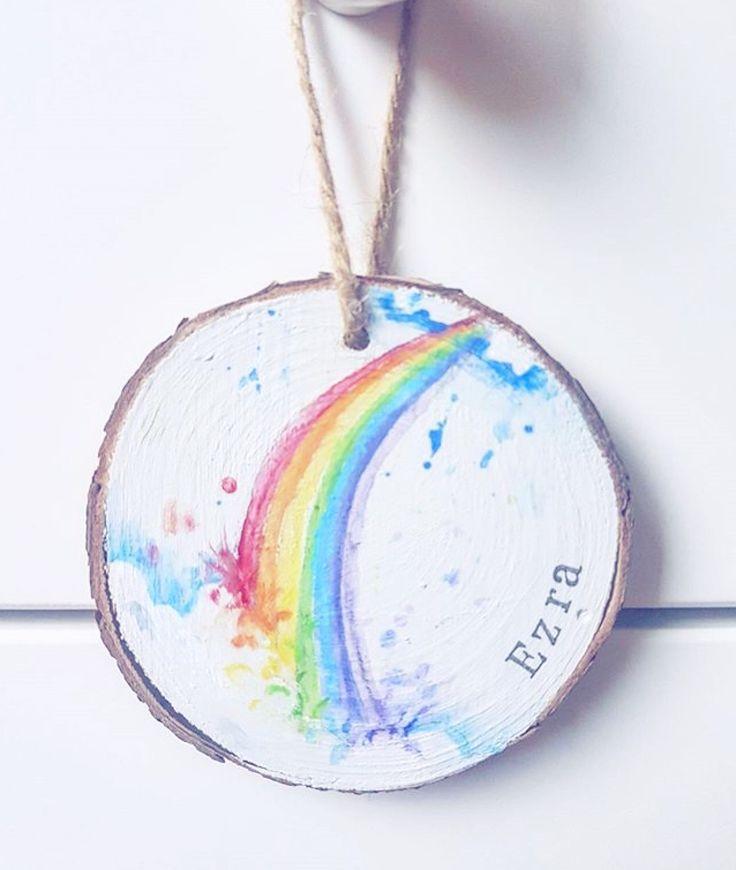 Handpainted rainbow wood slice for a new baby nursery with a rainbow decor theme.