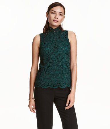 Dark green. Sleeveless lace blouse with a small stand-up collar and an opening at back of neck with covered buttons. Jersey lining.