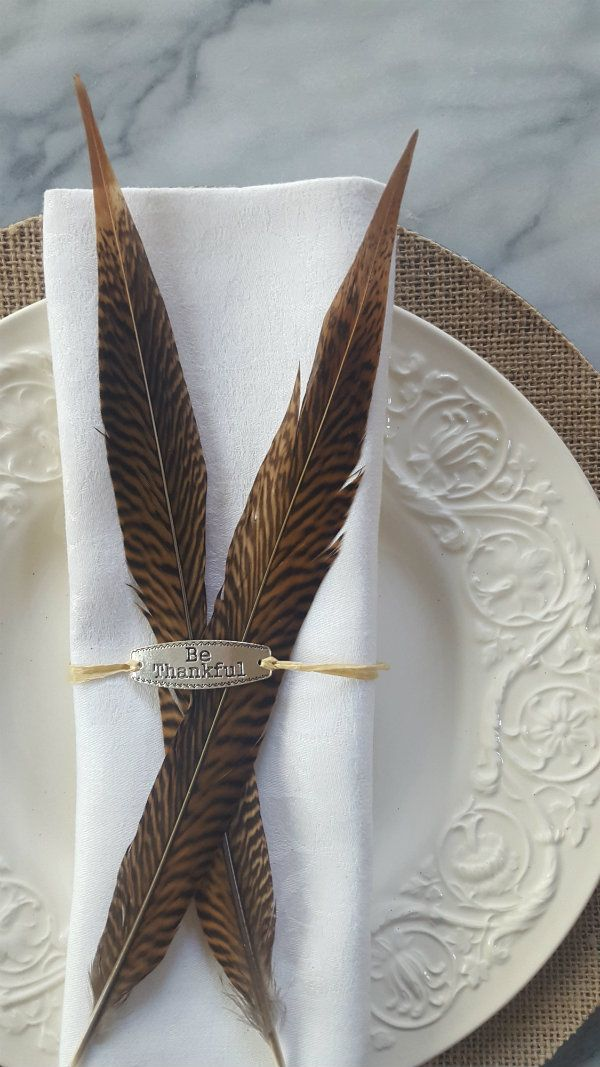 """Setting a beautiful Thanksgiving table. My starting point were these textural burlap chargers. Next, I wanted something personal for each guest, so the idea of the gorgeous pheasant feathers and """"Be Thankful"""" charms wrapped up together for each place setting was perfect!"""