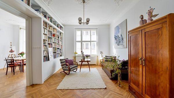 Průchod mezi jídelnou a obývacím pokojem byl rozšířen a zárubně jsou vyrobeny přesně podle těch původních. Knihovna je zhotovena na míru danému prostoru tak, aby na sebe nestrhávala pozornost, která v této místnosti patří retro nábytku a obrazu.