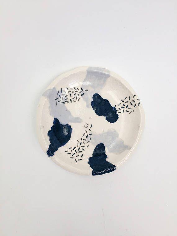 Ce plat de la bague en céramique a été à la main construit à l'aide de faïence blanche, vitrage avec underglaze noir et gris et ensuite effacer glaçage sur le dessus. Ensuite, il a été tiré deux fois dans un four électrique. L'utiliser pour organiser vos bijoux, plantes de l'air ou autres babioles!  La taille est 3,5 de diamètre  ** S'il vous plaît noter que chaque pièce est unique en son genre et donc des imperfections mineures peuvent être présentes.