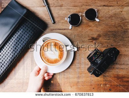 Top view of woman hand holding hot latte coffee with woman bag, camera ,sunglasses and pen on wooden table background, fashion and lifestyle concept