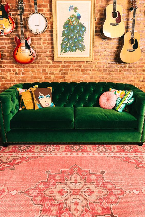 perfect forest green velvet sofa with bare brick walls, guitars and persian rug
