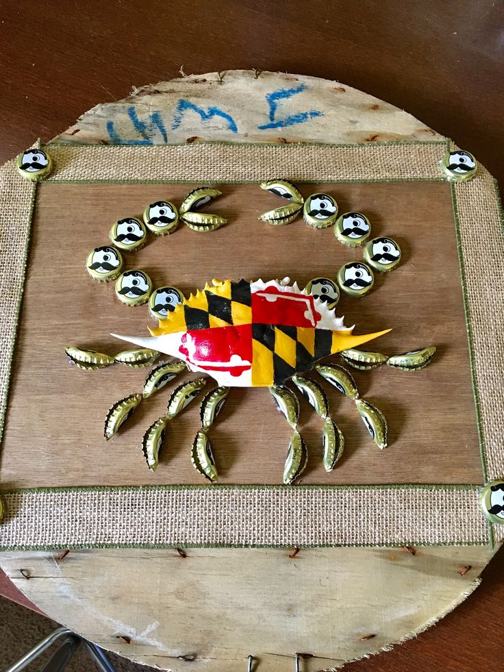 Using a crab basket lid, I attached a piece of thin plywood to the top. I painted a crab shell with the Maryland flag design, then glued it to the board. Natty Boh beer caps were squeezed in half to make the legs and claws of the crab, and Natty Boh caps formed the front claws. Perfect for a deck for the Baltimore crab lover!