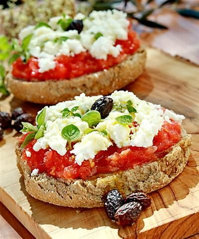 Dakos or ntakos! Also known as koukouvayia (=owl in greek)! Dip the barley rusks in water but not for too long! Chop one small tomato in tiny pieces for each rusk. Pour some olive oil and oregano and top it with feta or mizithra cheese! You can add olives if you want to :)