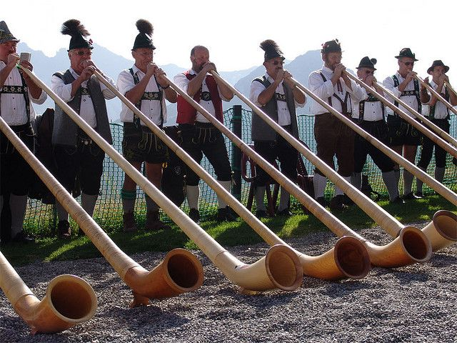 These long wooden horns are called an Alphorn or Alpine horn. Long time scholars believed that the horn had been derived from the roman Etrusem lituus (a coin celebrating the roman empire) because of the resemblance in shape of the picture on the coin. But there is no evidence for this.