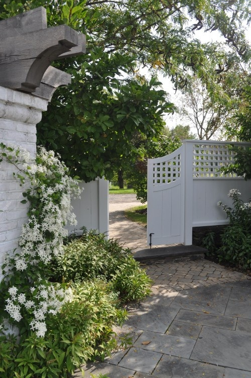 The graceful curve of this fence is such an elegant balance to the stone and pavers. Created by Milieu Design LLC.
