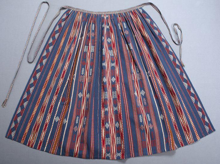 Randigt förkläde i inslagsrips och halvkrabba. Blå botten med mönsterränder i halvkrabba i rött och naturvitt samt ränder i grönt, vitt och blått, vissa med inslagsflotteringar i rött. Dessutom ränder i ikat/flamgarnsfärgat i rött och vitt.  Förklädet är rynkat upptill och kantat med ett grönt sidenband. Sidenbandet döljs på framsidan av ett plockat mönstervävt band med rött, gult och vitt mönster på blå botten, bandet har sytts ihop av två likadana 10 mm breda band. Det mönstrade bandet är…