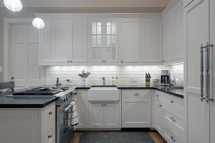 Small U shaped kitchen features white shaker cabinets paired with black countertops and a white subway tiled backsplash.
