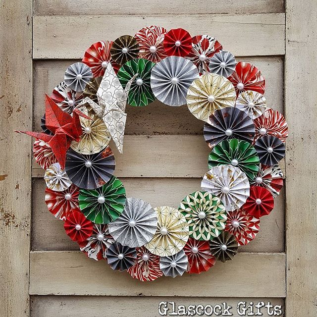 """Another of our 14"""" folded pinwheel rosette wreaths with paper cranes in the custom order for a Japanese restaurant. Red and green Japanese themed paper with pearl embellishments. #glascockgifts #origami #paper #paperart #paperwreaths #papercranes #custompaperart #christmas #christmaswreath"""
