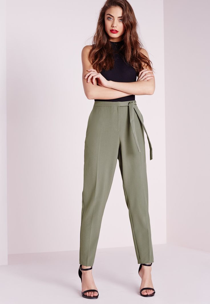 Up your game in these seriously glamorous high waist khaki trousers. With a tie belt and pocket details these put a sexy twist on tailored trousers. Let's face it, who doesn't need a pair of cigarette trousers in their life?! Style with the...