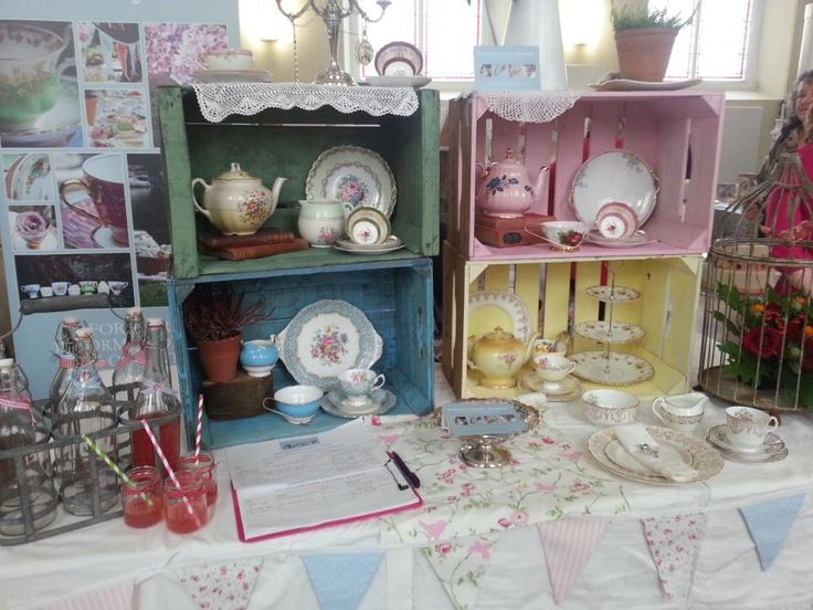 Vintage china displayed in colourful wooden crates