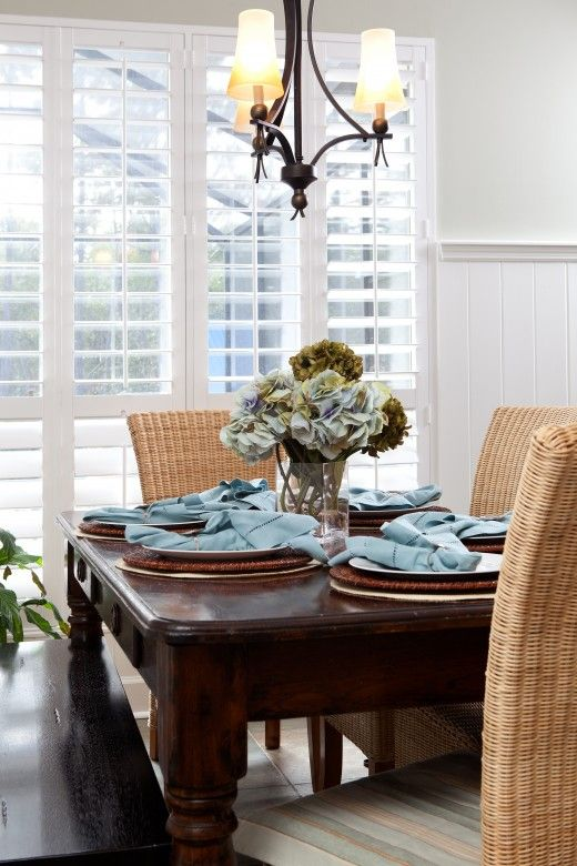 love the contrast of white plantation shutters, dark farmhouse table, and rattan chairs.
