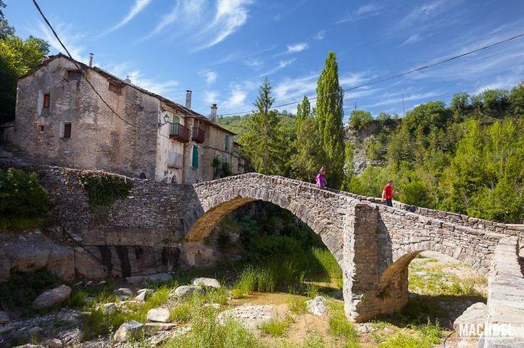 Dos personas cruzan el puente del pueblo de Montañana, Aragón, España