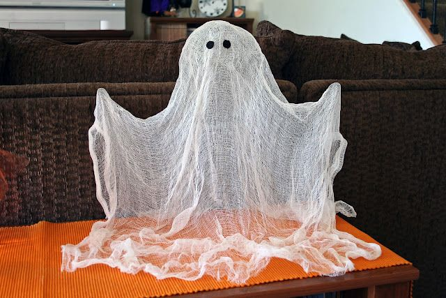 """Spray starch ghost. Drape gauze over a ghost """"form"""" (liter bottle for body, Styrofoam head, wire for arms), spray with starch, allow to dry."""