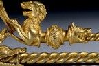 Gold fibula, of long-footed form decorated with the figure of a naked warrior, wearing a Celtic helmet, with scabbard suspended from his waist and carrying a sword (scabbard and pommel are both of La Tene type), with another figure of a hunting dog jumping up to him.  The eyes of both figures were originally inlaid with glass 'enamel'.  The arched bow has eight curls and the side panels are elaborated with running spirals and loops, also originally inlaid with blue glass 'enamel'.  Each end…