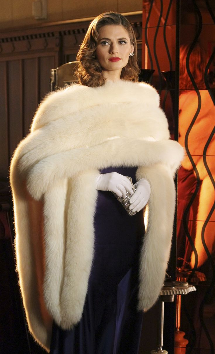 Elegant evening wear, perfect for a night at the opera or ballet. Fur throw, white gloves, black silk dress and perfect side parted hair