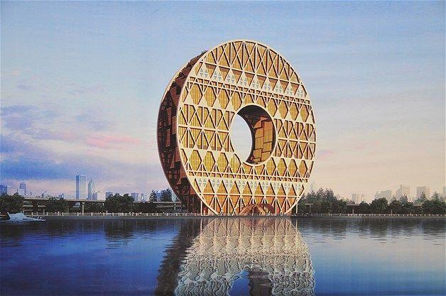 004 - Se trata del edificio del Yuan, más conocido como el edificio de la moneda, en Guangzhou, provincia de Guangdong, sur de China. Este edificio en forma de moneda cilíndrica está construido en la orilla del río de la Perla. Encargado por el Guangdong Plastics Exchange, el edificio de 138 metros de altura y con un agujero interior de 47 metros, está diseñado para parecerse a un viejo jade chino, una rueda de agua o el oro de la moneda china, todas las cuales se cree que traen buena suerte