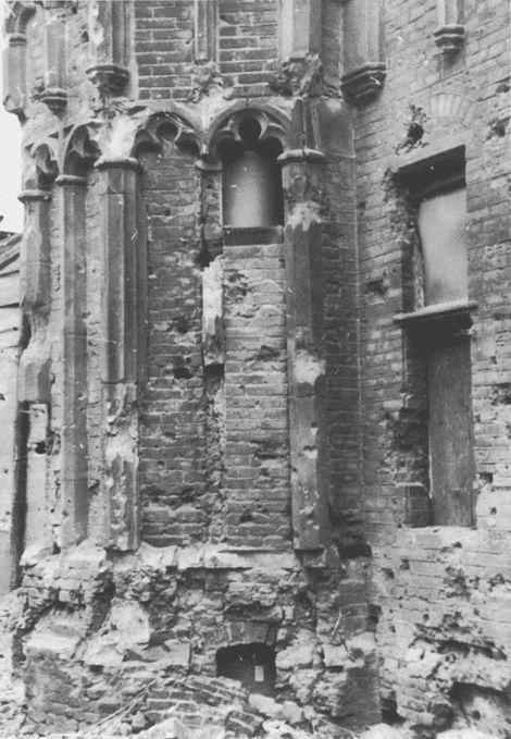 Bomschade aan de voet van de hoektoren van de Waag in Deventer, 1945.