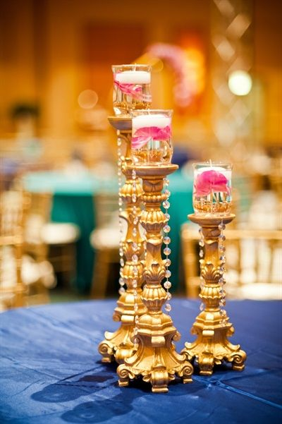 floating candle centerpieces on tall gold candleholders | Ashmi & Tushar's Sweet Gujarati Indian Wedding {Orlando, FL} - Gallery - TheBigFatIndianWedding.com