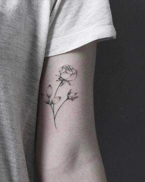 Hand poked rose tattoo on the left bicep.