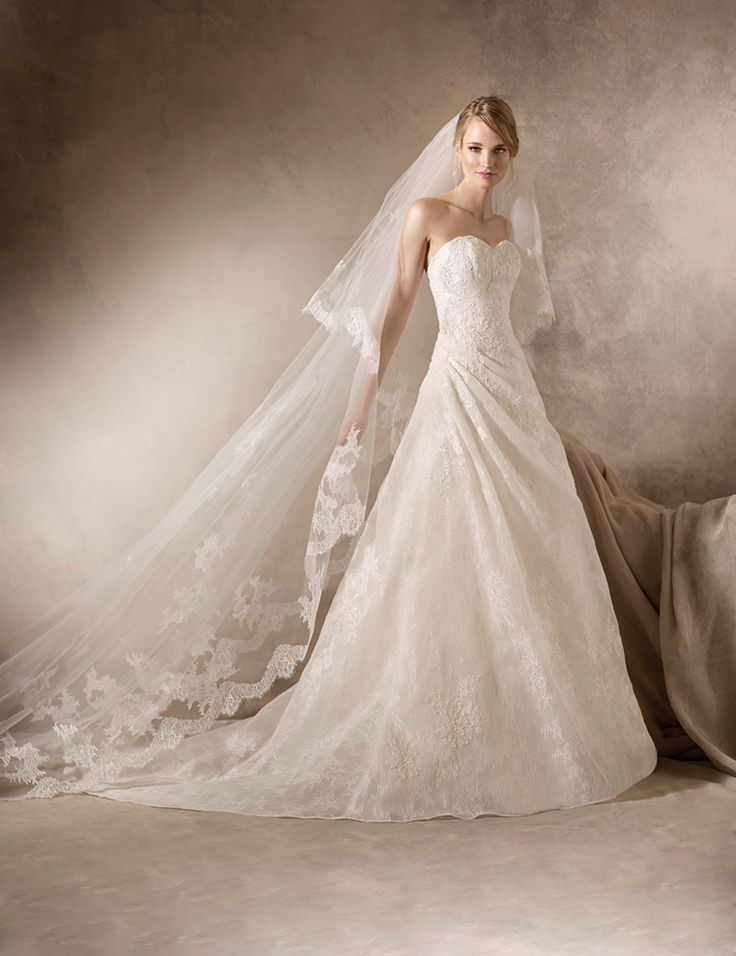 HENA - Romantic A-line wedding dress with sensual draping on the hip in Chantilly, lace, embroidery and gemstone appliqué.
