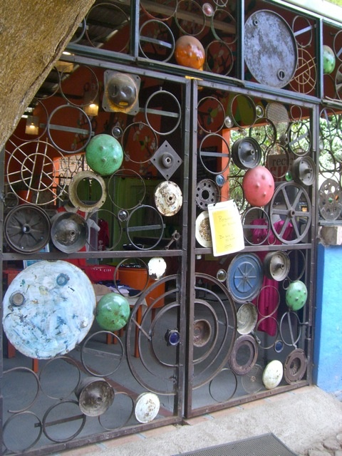 gate made of various found metal scraps, including hub caps