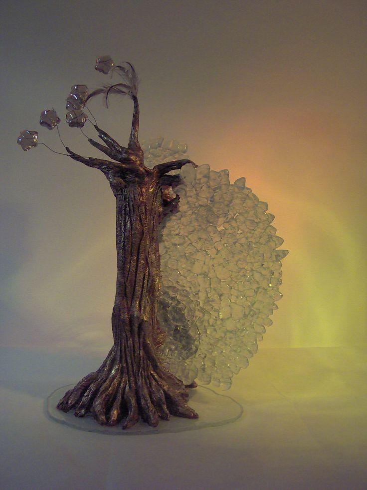 """SCULTURA LUMINOSA """"CHIOMA DI STELLE"""" Scultura luminosa realizzata in  terra refrattaria e  resina, cristallo fuso, vetro float sabbiato,vetro stampato, fili di metallo e piume.  Dimensioni: larghezza cm.30 altezza cm. 40"""