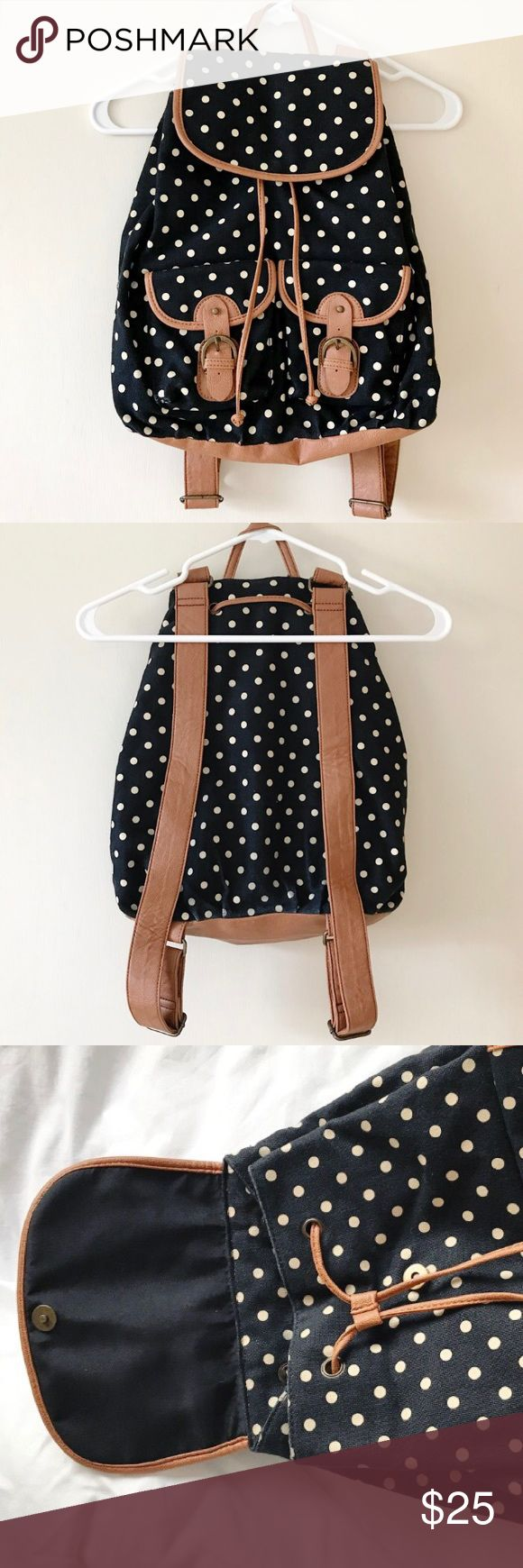 """ALDO Polka Dot Canvas Backpack ALDO Polka Dot Backpack. Navy canvas material with white polka dots. Straps and lining are a brown faux leather. Snap flap with drawstring opening. 2 outside pockets with buckles- 2 small pockets & 1 zip pocket inside. Flaws: minor signs of wear on the material on the back bottom. Otherwise in great condition!  ** Sorry, NO trades **  ** Please make offer using """"Offer"""" button ** Aldo Bags Backpacks"""