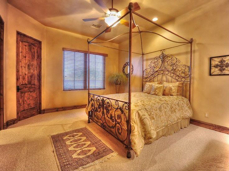 Mediterranean Guest Bedroom with flush light, Ceiling fan, Carpet, Stanton Metal Canopy Bed with Elegant Scrolls