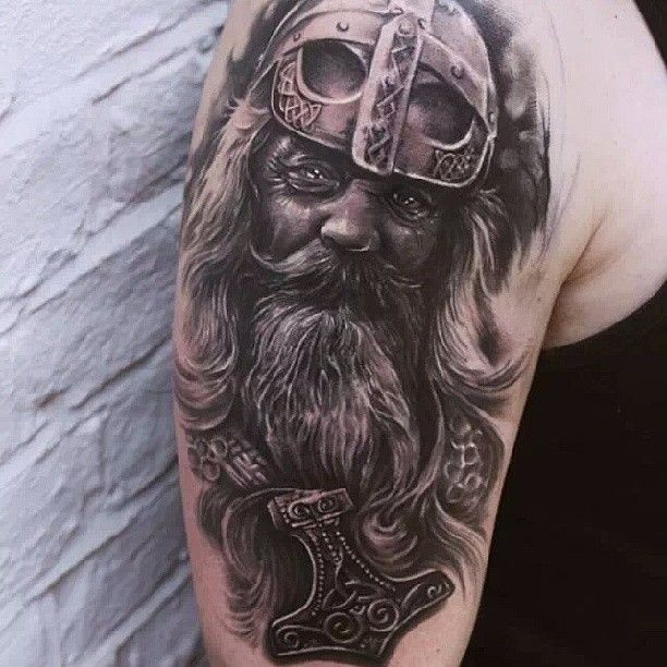 Black and white Viking warrior head tattoo on shoulder