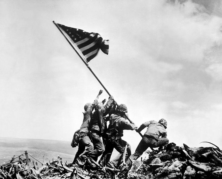 """Raising the Flag on Iwo Jima"""" . Five United States Marines and one sailor raising an American flag over Mount Suribachi during the Battle of Iwo Jima. By Joe Rosenthal, February 23, 1943"""
