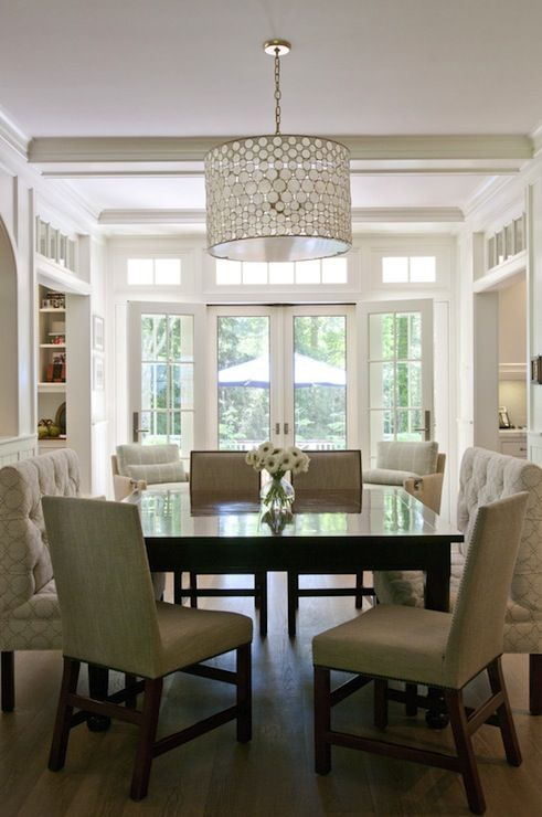 Lovely square dining room with Oly Studio Serena Drum Chandelier over glossy black square dining table surrounded by nailhead dining chairs and tufted dining benches. Beyond dining room is small lounge space filled with plush upholstered chairs and glass French doors and transom windows leading out to backyard.